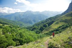 Trekking woman down valley in Picos de Europa Stock Images