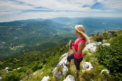 Trekking - woman hiking in mountains on a calm sumer day Stock Images