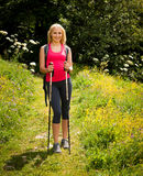 Trekking - woman hiking in mountains on a calm sumer day.  Royalty Free Stock Image