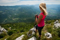 Trekking - woman hiking in mountains on a calm sumer day Stock Photo
