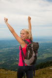 Trekking - woman hiking  in mountains on a calm sumer day being Royalty Free Stock Images