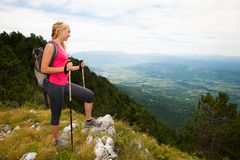 Trekking - woman hiking in mountains on a calm sumer day.  Stock Images