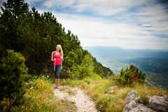 Trekking - woman hiking in mountains on a calm sumer day Royalty Free Stock Images