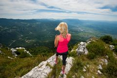 Trekking - woman hiking in mountains on a calm sumer day Stock Image