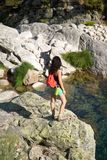 Trekking woman on a rock watching river Royalty Free Stock Images
