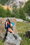 Trekkingsmädchen auf einem entspannenden Gebirgsfelsen stockbild