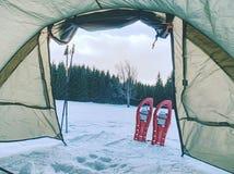 Trekkingstent tegen sneeuwlandschap wordt gebouwd dat Trek van de winterskialpinism over sneeuwbergpieken stock foto's