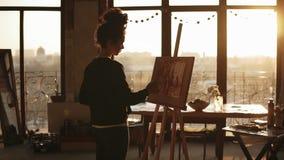 Trekt de volledig geconcentreerde verfijnde vrouwelijke kunstenaar in haar 20 ` s beeld op schildersezel in een kunststudio stock footage
