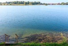 Trekt het kalme strand van het de zomermeer met hout aan het water Stock Foto