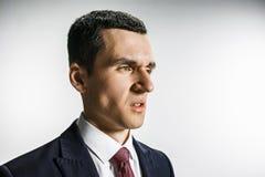 Trekvarts- stående av en affärsman med avsmakframsidan Säker professionell med piercingblick i förgrunden arkivbilder