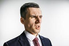 Trekvarts- stående av en affärsman med avsmakframsidan Säker professionell med piercingblick i förgrunden royaltyfria foton