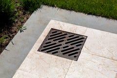 Trellis de drainage en métal dans un passage couvert de marbre image stock