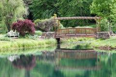 Trellised Garden Foot Bridge Reflection Mirror. This wooden arbor-like pedestrian foot bridge spans Lake Gardiner in Meadowlark Botanical Gardens, Vienna VA and Royalty Free Stock Photography