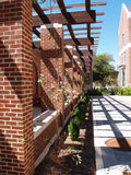 Trellised walkway by brick building Royalty Free Stock Photo