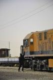 Trem alaranjado e mecânicos do trem que agitam as mãos Foto de Stock Royalty Free
