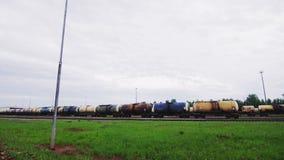 Trem com os reservatórios dos produtos petrolíferos na estrada de ferro sob o céu nebuloso vídeos de arquivo
