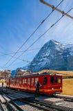 Trem da estrada de ferro de Jungfrau na estação de Kleine Scheidegg com pico de Eiger e de Monch imagens de stock royalty free