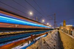 Trem de alta velocidade com borr?o de movimento no fundo da ponte de estrada de ferro na obscuridade fotografia de stock