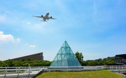 Trem de aterrissagem de distribuição do avião comercial comercial sobre o parque da expo de Taipei a aterrar em Songshan Airpor foto de stock