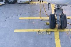Trem de aterrissagem de um avião de passageiros moderno - pneus de um plano - tiro ascendente próximo Rodas do avião com calços e fotografia de stock royalty free
