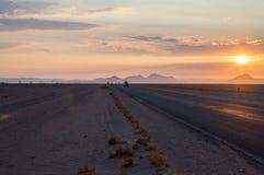 Trem de condução de carros em uma estrada no deserto no nascer do sol imagem de stock royalty free