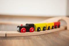 Trem de madeira do brinquedo na estrada de ferro com ponte de madeira Limpe o assoalho laminado fotos de stock