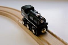 Trem de madeira preto do brinquedo da criança nas trilhas de madeira imagem de stock royalty free