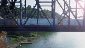 Trem de mercadorias aéreo da carga do perfil na ponte da estrada de ferro video estoque