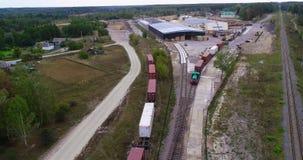 Trem de mercadorias perto da fábrica de woodworking, trem de mercadorias perto da fábrica Muita maquinaria pesada na jarda do filme