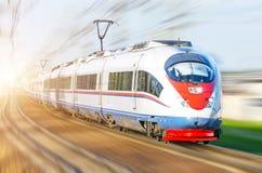 Trem de passageiros de alta velocidade que apressa-se através do trilho em Europa fotografia de stock