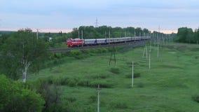 Trem de passageiros que corre no campo entre árvores verdes, Rússia filme