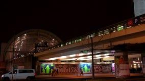 Trem de S-Bahn que deixa a estação de Alexanderplatz na inclinação da noite para baixo da torre da televisão, Berlim, Alemanha filme