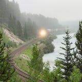 Trem distante ao longo do rio da montanha na névoa Imagem de Stock Royalty Free