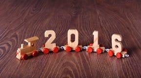 Trem do ano novo 2016 no fundo de madeira Fotos de Stock Royalty Free