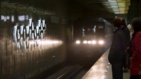 Trem e povos de vinda que esperam o na estação de metro Transporte do metro que chega à estação de metro com muitos video estoque