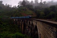 Trem na ponte de nove arcos na névoa foto de stock