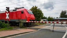 Trem no cruzamento de estrada de ferro em Alemanha Foto de Stock