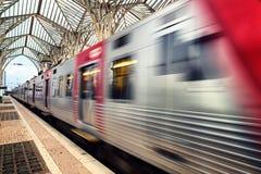 Trem obscuro que atravessa rapidamente o estação de caminhos-de-ferro de Lisboa Oriente foto de stock