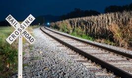 Trem próximo com sinal do cruzamento de estrada de ferro Imagens de Stock