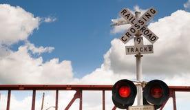 Trem que passa a cruzamento de estrada de ferro o piscamento das luzes de advertência Imagens de Stock