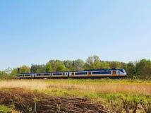 Trem que passa em um campo aberto imagens de stock
