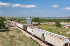 Trem que passa o elevador de grão velho em South Dakota Fotos de Stock Royalty Free