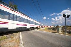 Trem que passa a passagem de nível Fotografia de Stock