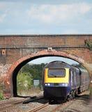 Trem que vai sob a ponte Foto de Stock
