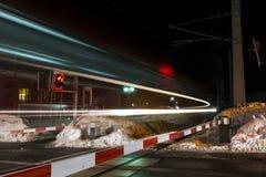 Trem rápido que passa pelo cruzamento de estrada de ferro Imagem de Stock Royalty Free