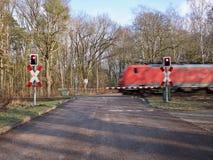 Trem vermelho que apressa-se através de uma passagem de nível Imagens de Stock
