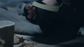 Trembling beggar opening Bible, searching salvation, faith in god, enlightenment. Stock footage stock video