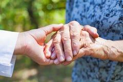 Trembling elderly hands. Close up medical doctor holding elderly female`s trembling hands Stock Photo