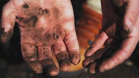 Trembling hands in the dirt. The theme of the homeless. Boom. Hopelessness. Close-up.
