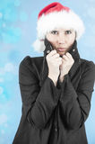 Trembling in the winter cold. Beautiful woman with a Christmas hat trembling being cold inthe winter time Royalty Free Stock Images